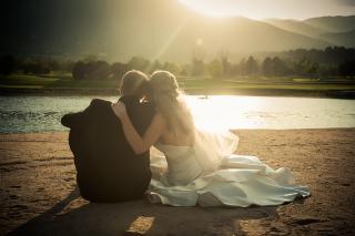 Wedding couple sitting on sand near lake