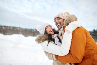 Couple laughing and hugging in snow